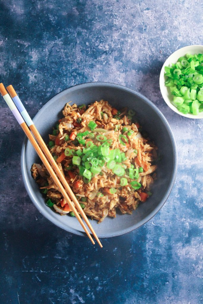 fried rice in a bowl, garnished with spring onions.
