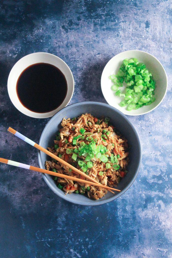 Bowl of chicken fried rice with two smaller bowls containing soy sauce and diced green onion, arranged in the shape of Mickey Mouse.